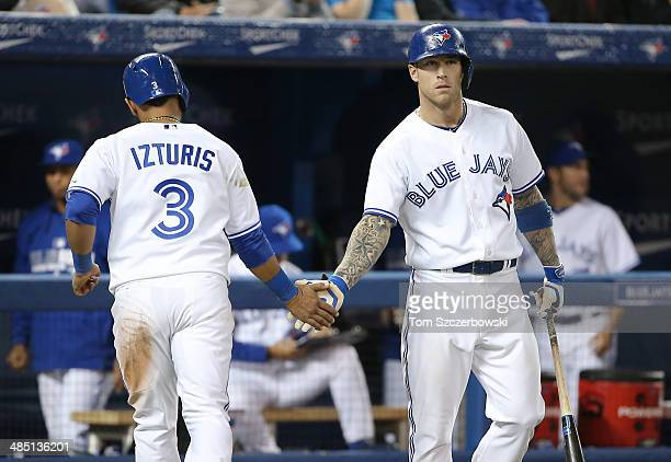 Maicer Izturis of the Toronto Blue Jays is congratulated by Brett Lawrie after scoring a run in the fifth inning during MLB game action against the...