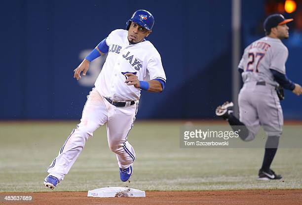 Maicer Izturis of the Toronto Blue Jays races around second base to score a run on an RBI double by Jose Bautista in the first inning during MLB game...