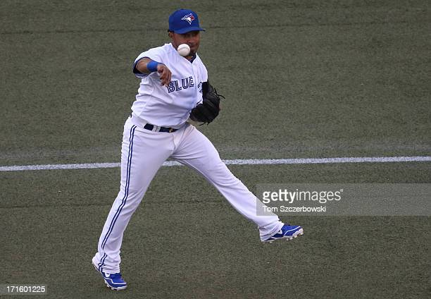 Maicer Izturis of the Toronto Blue Jays throws out a baserunner in the first inning during MLB game action against the Colorado Rockies on June 18...