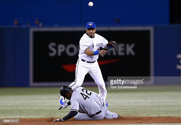 Maicer Izturis of the Toronto Blue Jays turns a double play in the fifth inning during MLB game as Alejandro De Aza of the Chicago White Sox slides...