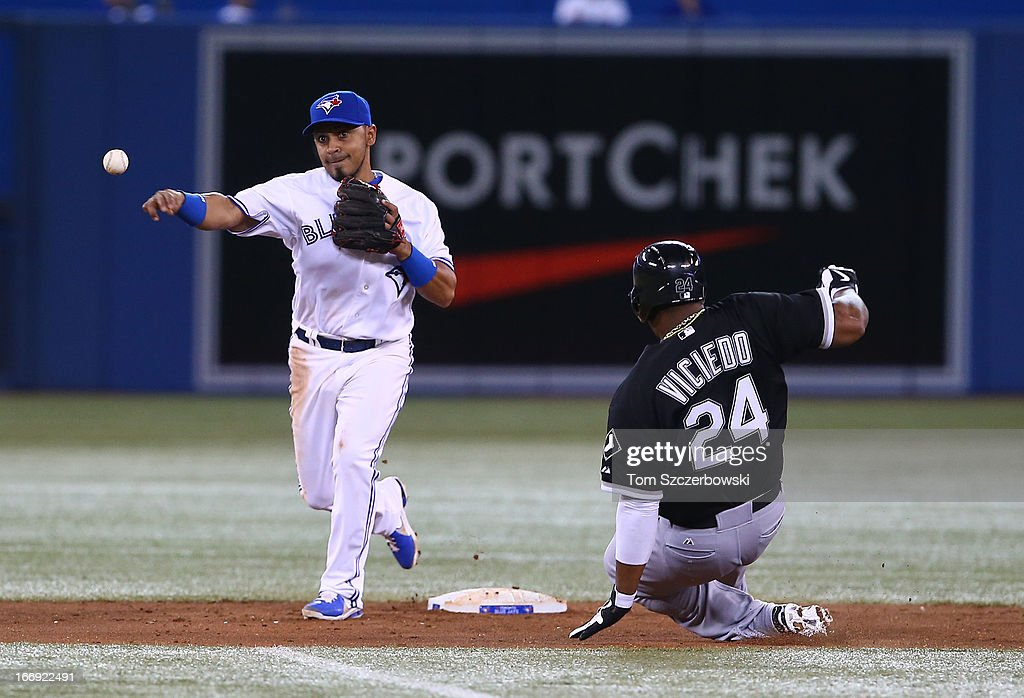Maicer Izturis #3 of the Toronto Blue Jays turns a double play in the fifth inning during MLB game action as Dayan Viciedo #24 of the Chicago White Sox slides on April 18, 2013 at Rogers Centre in Toronto, Ontario, Canada.
