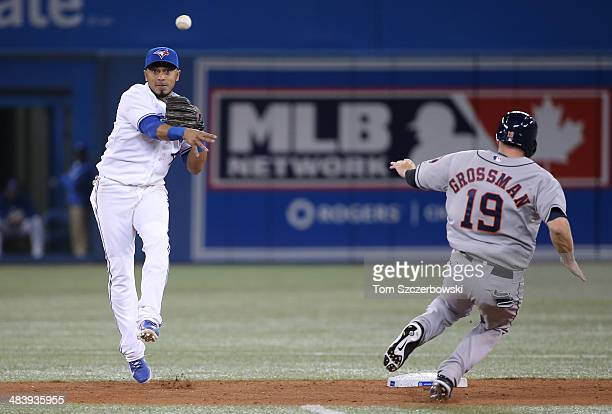 Maicer Izturis of the Toronto Blue Jays turns a double play in the ninth inning during MLB game action as Robbie Grossman of the Houston Astros...