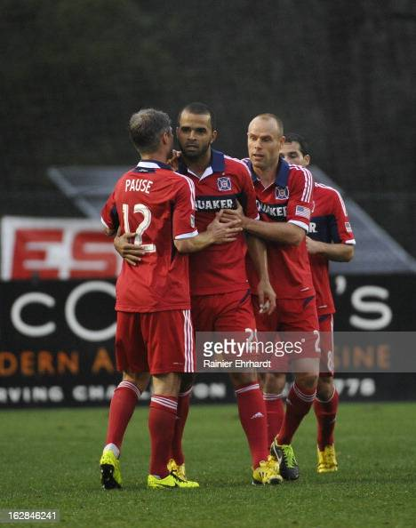 Maicon Santos of the Chicago Fire celebrates with teammates Joel Lindpere and Logan Pause after scoring a goal during the second half of the Carolina...