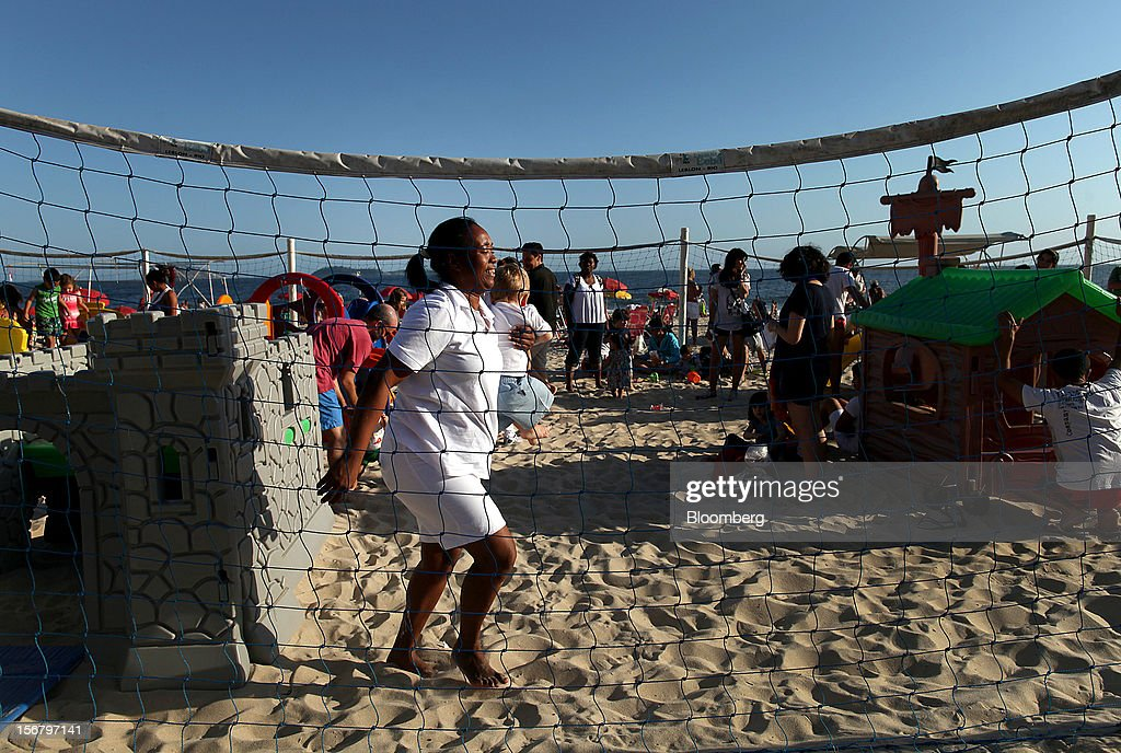 A maid carries a child at the Baixo Bebe beach playground in Rio de Janeiro, Brazil, on Monday, Nov. 19, 2012. With unemployment in Latin America's biggest economy at record lows, poor women who for decades formed a pool of cheap domestic labor for the middle and upper classes are pursuing better-paying, higher-skilled jobs. Photographer: Dado Galdieri/Bloomberg via Getty Images