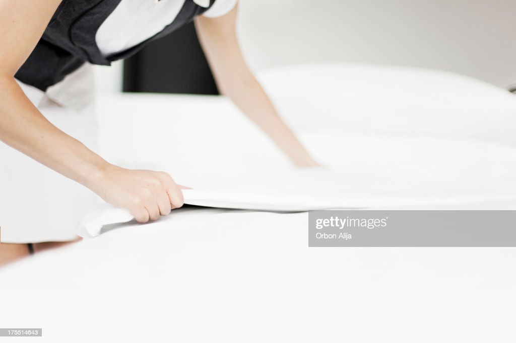Maid Changing Sheets in a Hotel Room