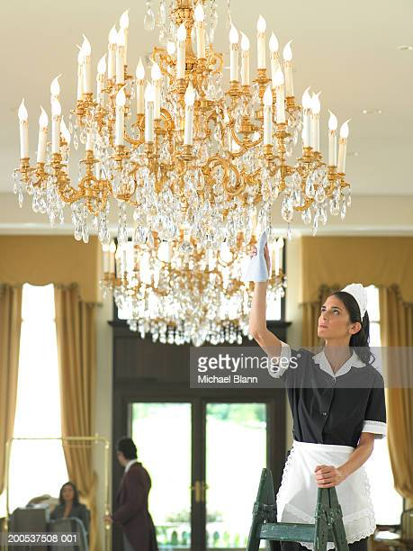 Maid cleaning chandelier in hotel foyer
