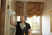 Maid clearing glass door in hotel bathroom