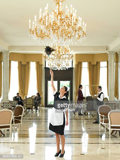 Maid dusting chandelier in hotel foyer