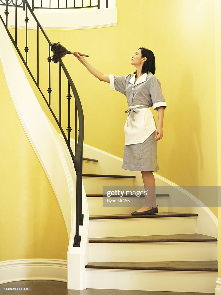 Maid dusting railing on stairway, side view : Stock Photo