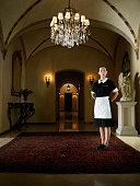 Maid in uniform standing in hallway