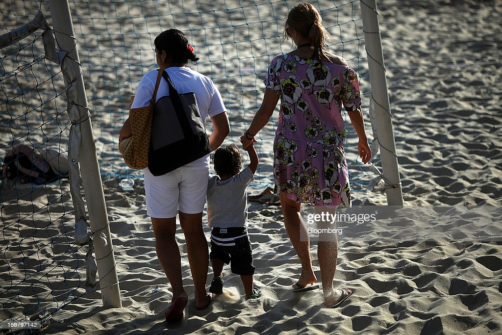 A maid, left, walks with a child in the sand at the Baixo Bebe beach playground in Rio de Janeiro, Brazil, on Monday, Nov. 19, 2012. With unemployment in Latin America's biggest economy at record lows, poor women who for decades formed a pool of cheap domestic labor for the middle and upper classes are pursuing better-paying, higher-skilled jobs. Photographer: Dado Galdieri/Bloomberg via Getty Images
