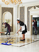 Maid mopping hotel foyer, male staff cleaning in background
