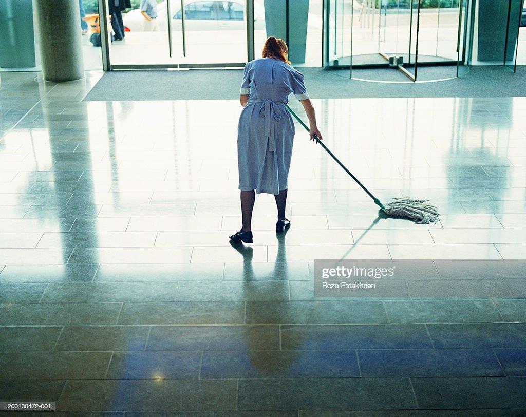 Maid mopping hotel lobby floor