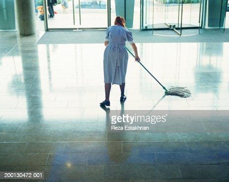 Maid mopping hotel lobby floor : Stock Photo