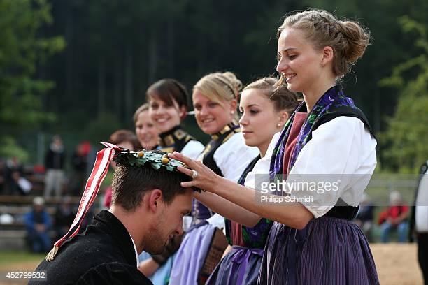 A maid of honor crowns the winner Kilian Wenger with a wreath after the Alpine Wrestling Festival BruenigSchwinget at the top of the Bruenig Pass on...