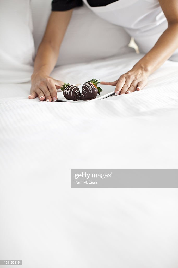 Maid placing plate of strawberries on bed : Stock Photo