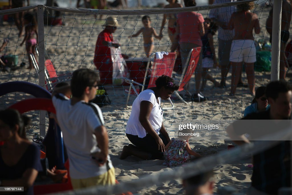 A maid plays in the sand with a child at the Baixo Bebe beach playground in Rio de Janeiro, Brazil, on Monday, Nov. 19, 2012. With unemployment in Latin America's biggest economy at record lows, poor women who for decades formed a pool of cheap domestic labor for the middle and upper classes are pursuing better-paying, higher-skilled jobs. Photographer: Dado Galdieri/Bloomberg via Getty Images