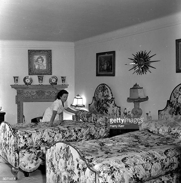 A maid smooths out the counterpane in the bedroom in which screen icon Marilyn Monroe will sleep during her stay in England The star has taken a...