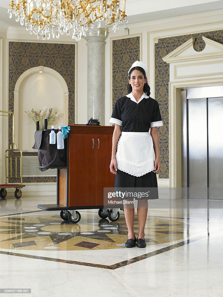 Maid standing by cleaning trolley in hotel foyer, smiling, portrait