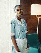 Maid standing in hotel room, portrait