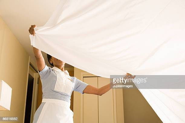 Maid straightening bed sheet