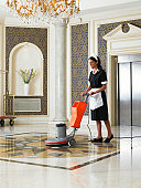 Maid vacuuming hotel foyer