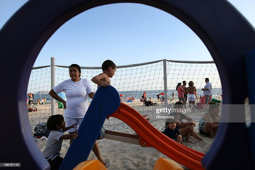 A maid watches children go down a slide at the Baixo Bebe beach playground in Rio de Janeiro, Brazil, on Monday, Nov. 19, 2012. With unemployment in Latin America's biggest economy at record lows, poor women who for decades formed a pool of cheap domestic labor for the middle and upper classes are pursuing better-paying, higher-skilled jobs. Photographer: Dado Galdieri/Bloomberg via Getty Images