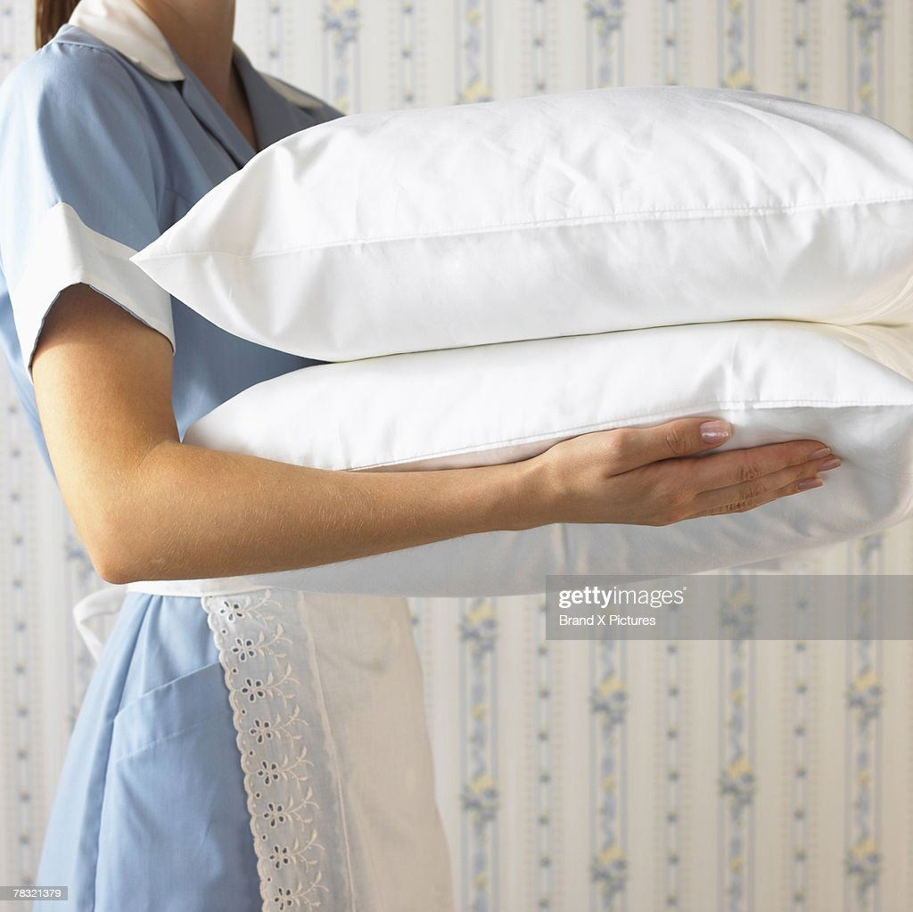 Maid with pillows : Stock Photo