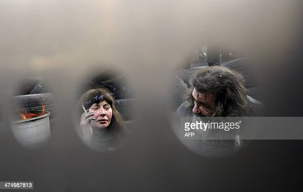 Maidan protesters are seen through the holes in a police shield in central Kiev on February 26 2014 Ukraine's proWestern interim leaders were set to...