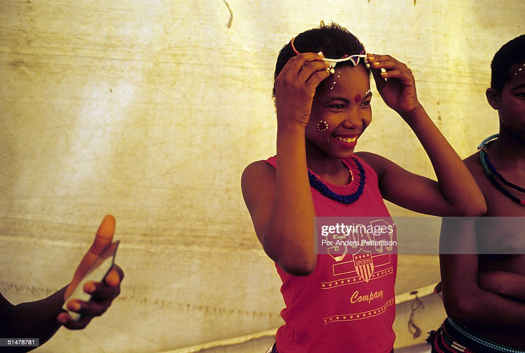 A maiden dresses and puts on makeup to prepare for the annual Reed Dance September 11, 2004 in Nongoma in rural Natal, South Africa. About 20,000 fellow maidens from all over South Africa has arrived to dance for Zulu King Goodwill Zwelethini at the Enyokeni Royal Palace in Kwa-Nongoma about 350 kilometers from Durban. The girls come to the kingdom to declare their virginity and the ceremony encourages girls and young women to abstain from sexual activity to curb the spread of HIV/AIDS.