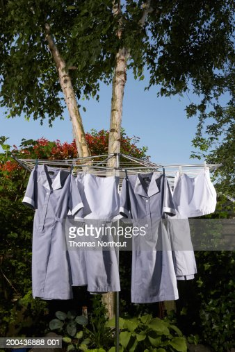 Maid's uniforms hanging from clothesline outdoors : Stock Photo
