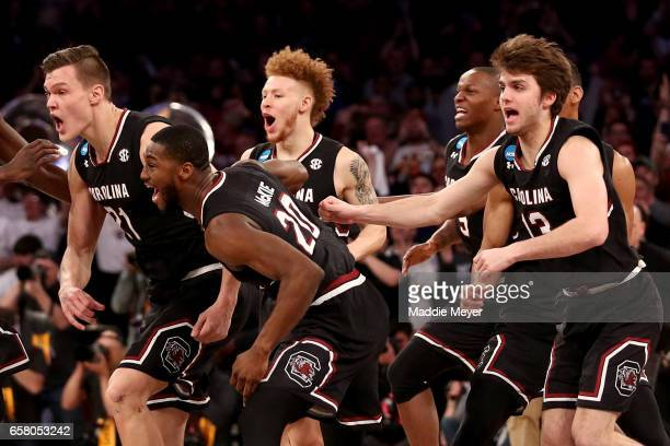 Maik Kotsar and Justin McKie of the South Carolina Gamecocks celebrate with their teammates after defeating the Florida Gators with a score of 77 to...