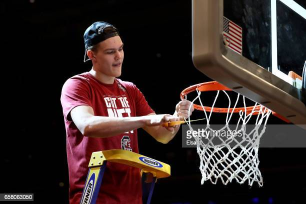 Maik Kotsar of the South Carolina Gamecocks celebrates by cutting down the net after defeating the Florida Gators with a score of 77 to 70 to win the...