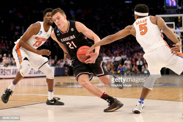 Maik Kotsar of the South Carolina Gamecocks drives to the basket against Kevarrius Hayes and KeVaughn Allen of the Florida Gators in the first half...