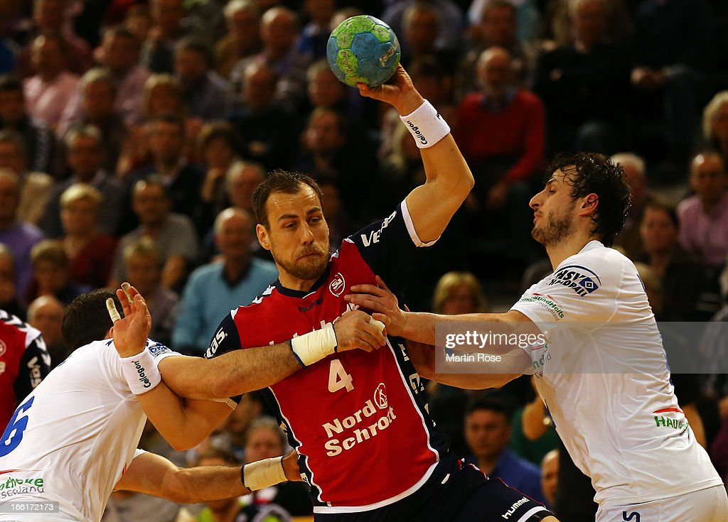Maik Machulla of Flensburg (C) is challenged by Blazenko Lakovic (L) and <a gi-track='captionPersonalityLinkClicked' href=/galleries/search?phrase=Domagoj+Duvnjak&family=editorial&specificpeople=2289188 ng-click='$event.stopPropagation()'>Domagoj Duvnjak</a> (R) of Hamburg during the DKB Handball Bundesliga match between SG Flensburg-Handewitt and HSV Hamburg at Flens Arena on April 9, 2013 in Flensburg, Germany.