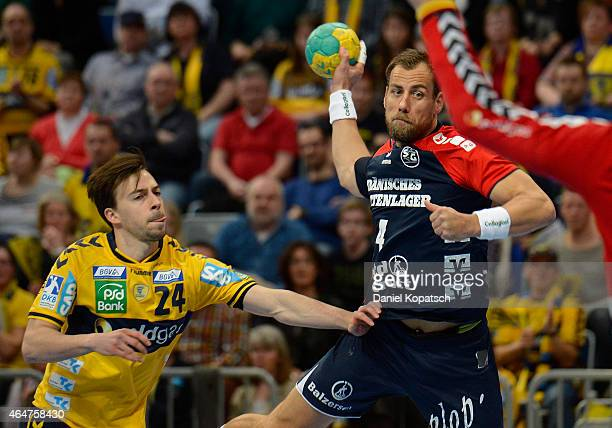 Maik Machulla of Flensburg is challenged by Patrick Groetzki of RheinNeckar Loewen during the DKB HBL Bundesliga match between RheinNeckar Loewen and...