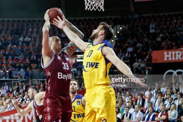 Maik Zirbes of Bayern Muenchen and Philipp Schwethelm of Oldenburg battle for the ball during the easyCredit BBL Basketball Bundesliga match between...