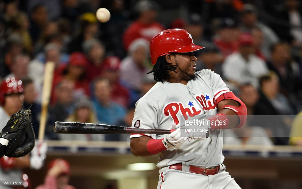 Maikel Franco #7 of the Philadelphia Phillies is hit with a pitch during the fifth inning of a baseball game against the San Diego Padres at PETCO Park on August 15, 2017 in San Diego, California.