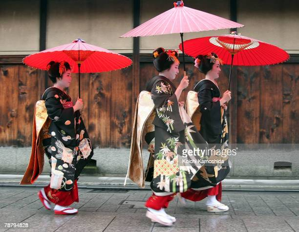 Maiko and Geiko walk with an umbrella during a New Year's ceremony at the Gion Kobu Kaburenjo on January 7 2008 in Kyoto Japan The traditional...