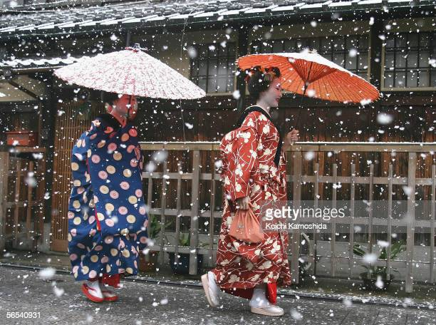 Maiko and Geisha walk in the snow at Gion on January 7 2006 in Kyoto Japan The ancient city Kyoto attracts the largest number of visitors in Japan...