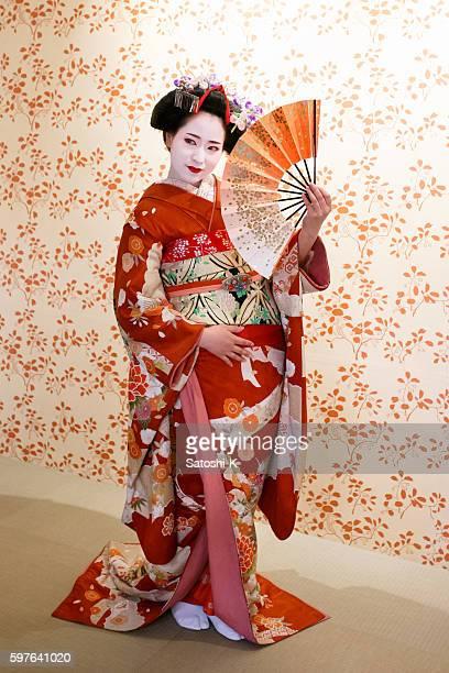 Maiko girl posing with Japanese folding fan