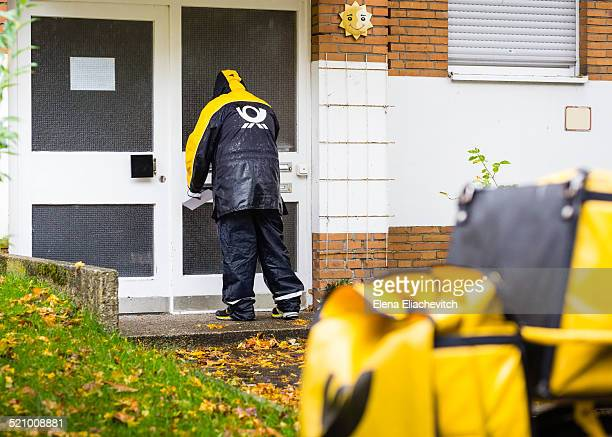 Mail Carrier brings letters during pouring rain Hannover Germany