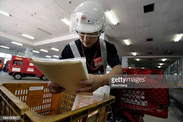 A mail carrier loads mail onto his motorcycle from a plastic crate at a Japan Post Co post office in Tokyo Japan on Monday Oct 26 2015 Japan Post...