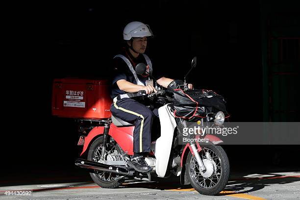 A mail carrier rides a motorcycle as he departs from a Japan Post Co post office in Tokyo Japan on Monday Oct 26 2015 Japan Post Holdings and its...