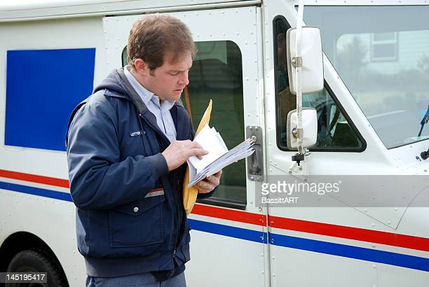 Mail carrier sorting mail near delivery truck