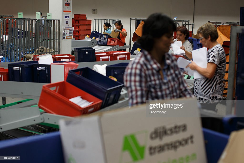 Mail crates move along a conveyor belt as employees sort envelopes at the PostNL NV sorting center in Nieuwegein, Netherlands, on Friday, Sept. 27, 2013. PostNL NV rose the most in two months on Sept. 19 after the Dutch postal operator raised its full-year forecast and announced higher prices for stamps. Photographer: Jasper Juinen/Bloomberg via Getty Images