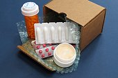 Horizontal image of prescription medications shipped in a cardboard box from a mail order (online) compound pharmacy
