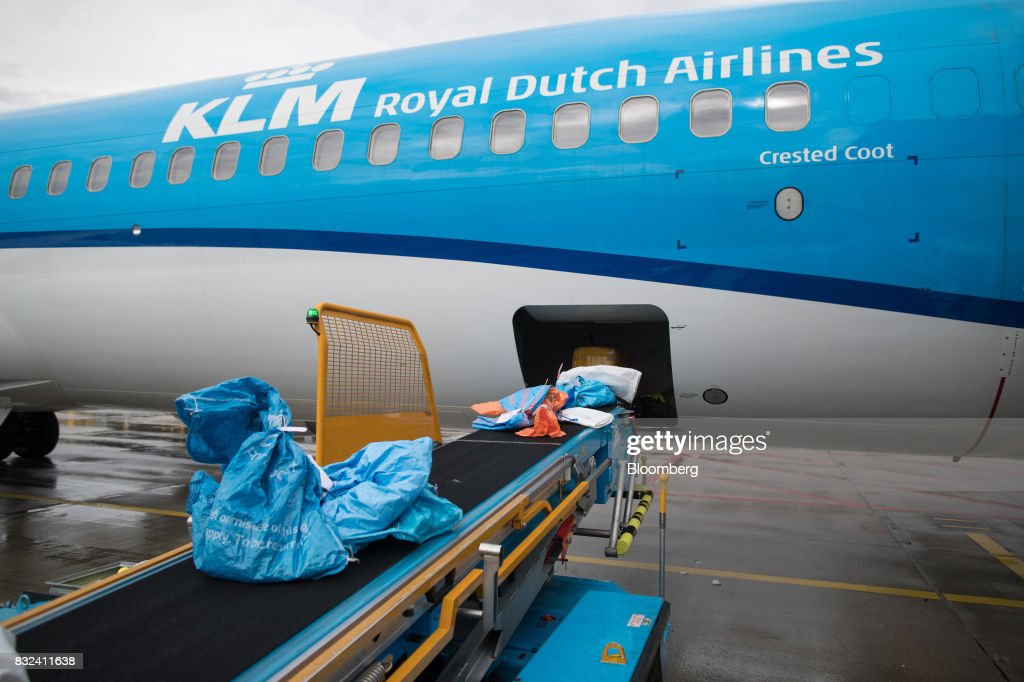 Mail sacks and packages pass along a conveyor as they are loaded onto an aircraft operated by KLM, the Dutch arm of Air France-KLM Group, on the tarmac at Schiphol airport in Amsterdam, Netherlands, on Tuesday, Aug. 15, 2017. Delta Air Lines Inc., China Eastern Airlines Corp. and Air France-KLM Group are reaching for their checkbooks to forge a deeper global alliance. Photographer: Jasper Juinen/Bloomberg via Getty Images