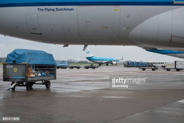 Mail sacks and packages sit in a trailer beneath an aircraft operated by KLM the Dutch arm of Air FranceKLM Group at Schiphol airport in Amsterdam...