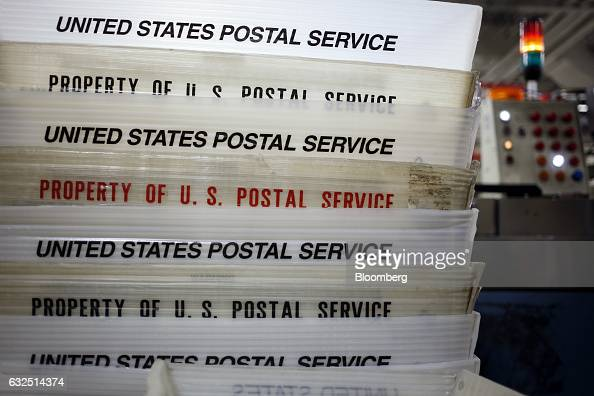 Mail trays sit stacked beside an automated sorting machine at the United States Postal Service sorting center in Louisville Kentucky US on Friday Jan...